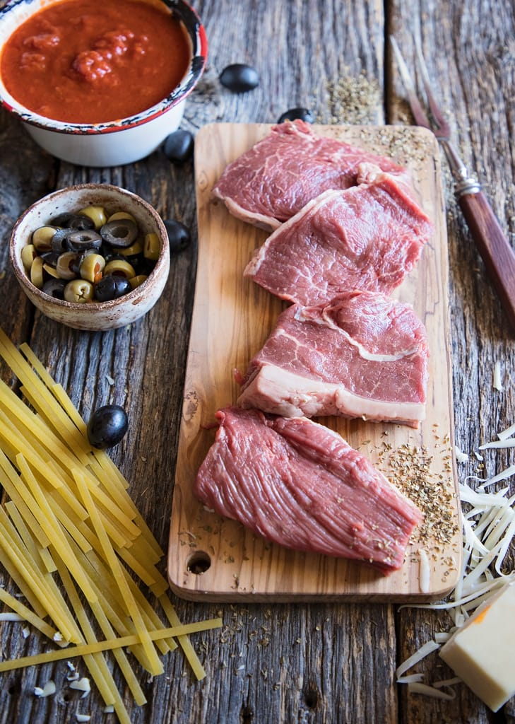 steaks on a cutting board with pasta, olives, and sauce on the side