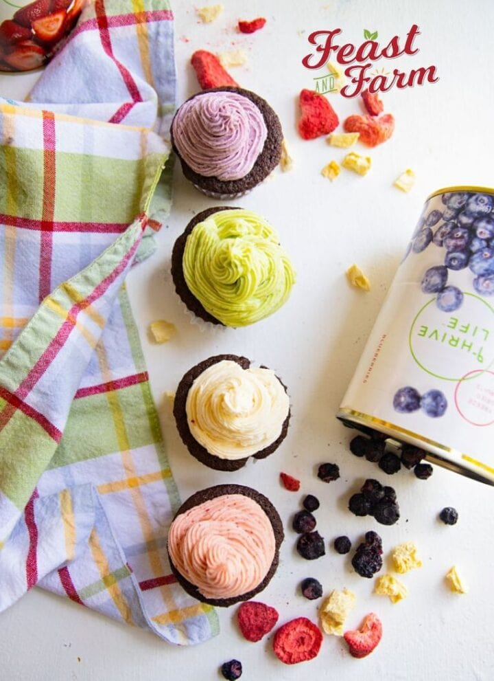 four cupcakes in a line with open cans of freeze dried fruit on a table with a colored napkin