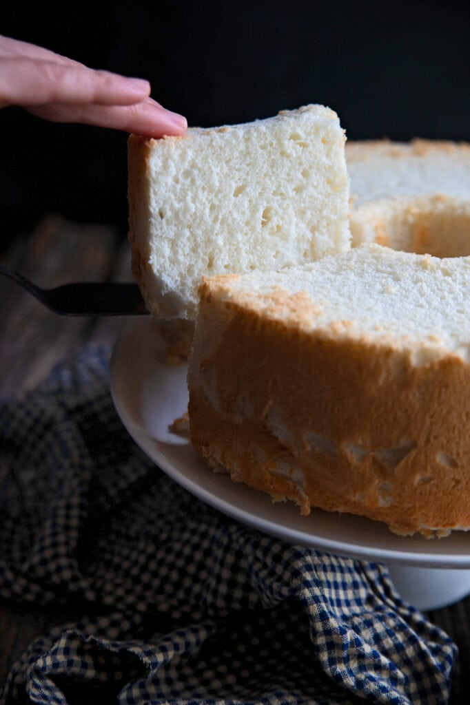 a slice of angel food cake being lifted from the whole cake