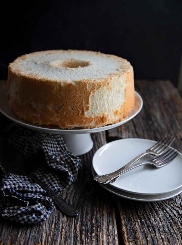 round angel food cake on a cake plate with a small white plate and two forks
