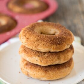 three baked apple cider donuts on a plate