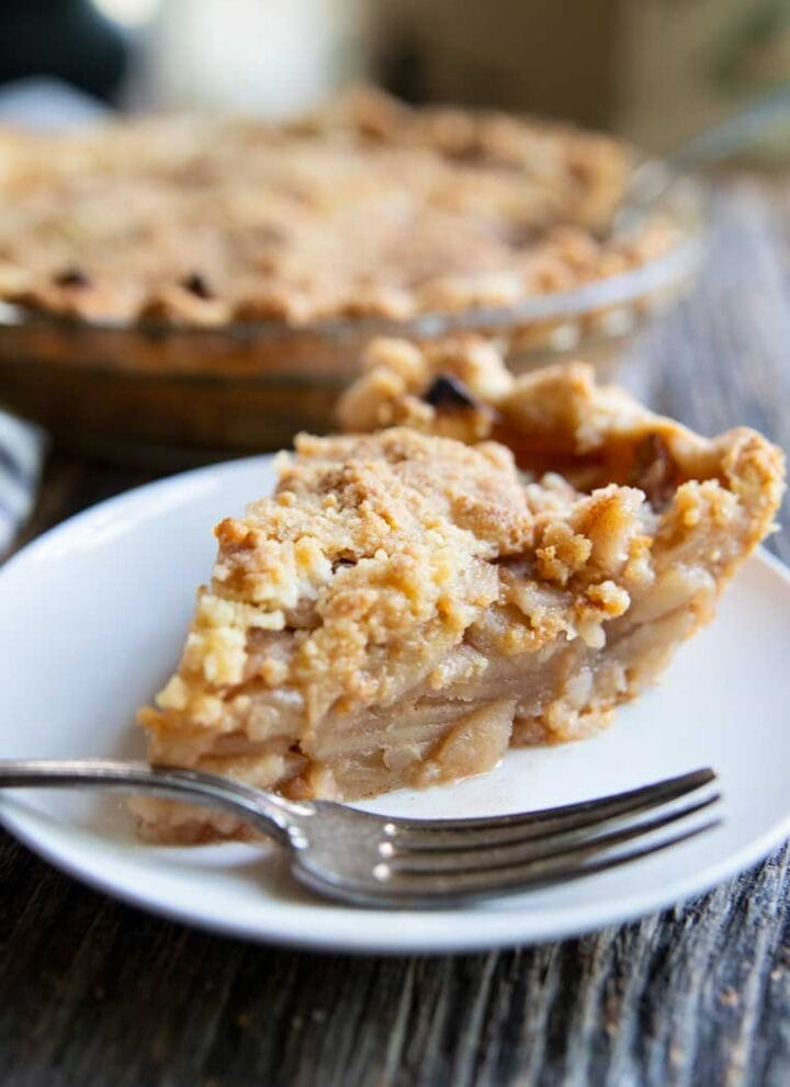 a slice of apple pie on a plate with a fork