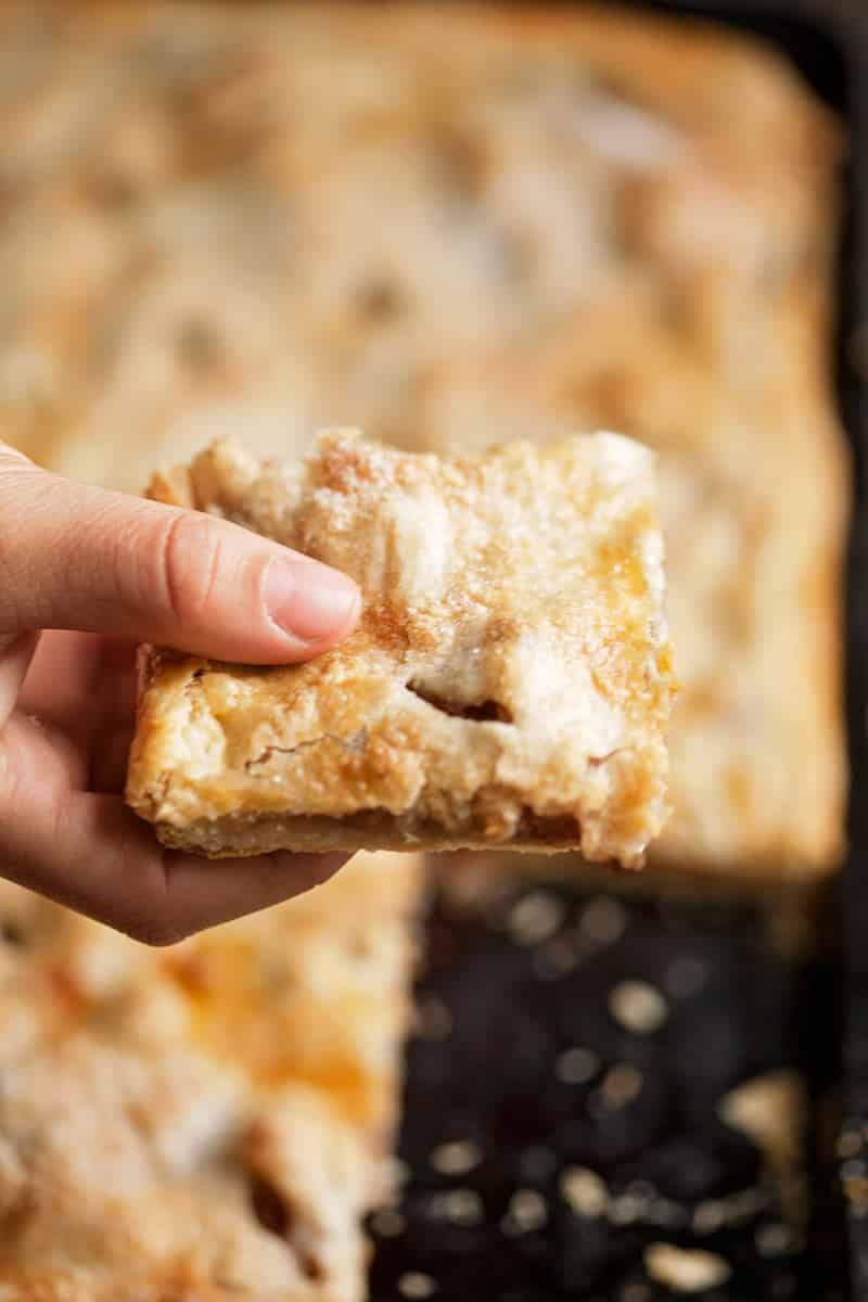someone holding a piece of apple slab pie