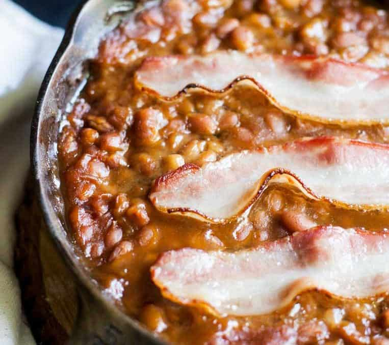 a skillet of baked beans with bacon slices on top