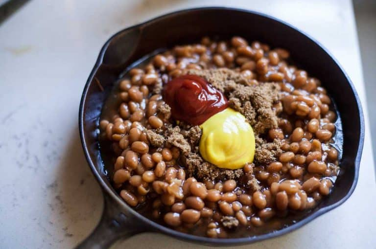 A skillet of baked beans with dollops of mustard, ketchup and brown sugar before being stirred together