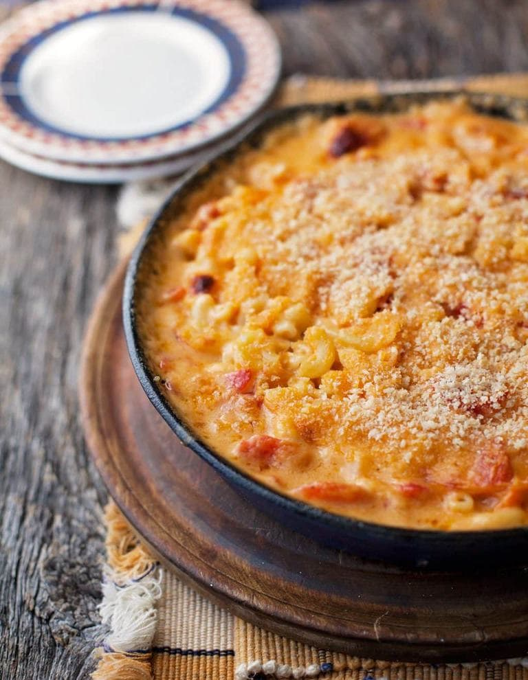 a skillet of mac and cheese with tomatoes with bread crumbs on top and two plates in the background