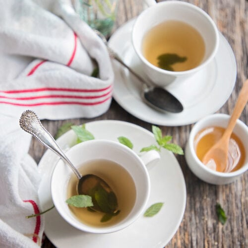 two cups of peppermint tea on a wooden table