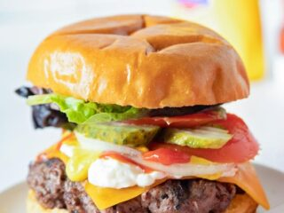 a bison burger on a table with all the toppings