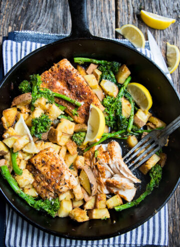 a skillet of blackened mahi mahi with roasted sweet potatoes and broccolini