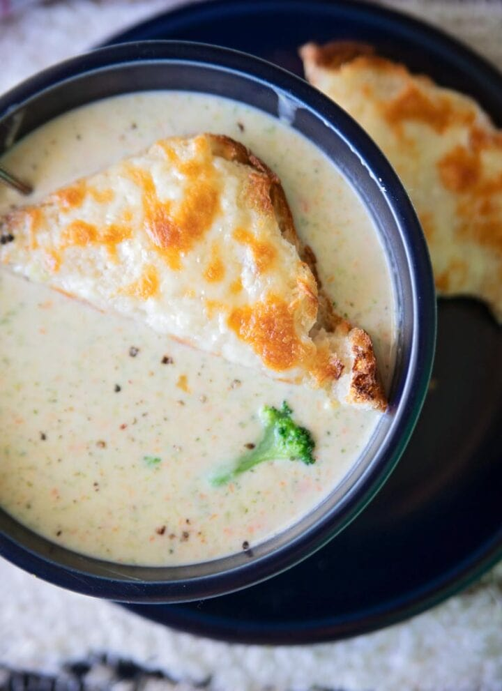 a bowl of broccoli cheddar soup with cheesy toast on top