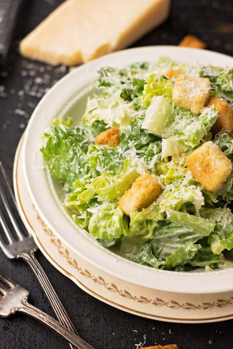 A bowl of caesar salad in a white bowl with a  fork on the side