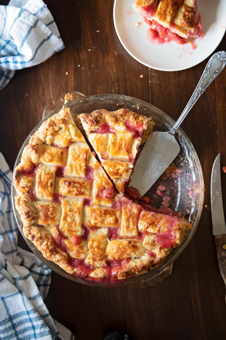 a tart cherry pie on a table with a slice missing, one slice cut and a pie server