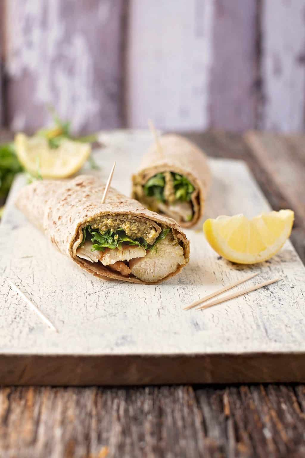 two chicken pesto wraps on a cutting board with two lemon wedges and toothpicks