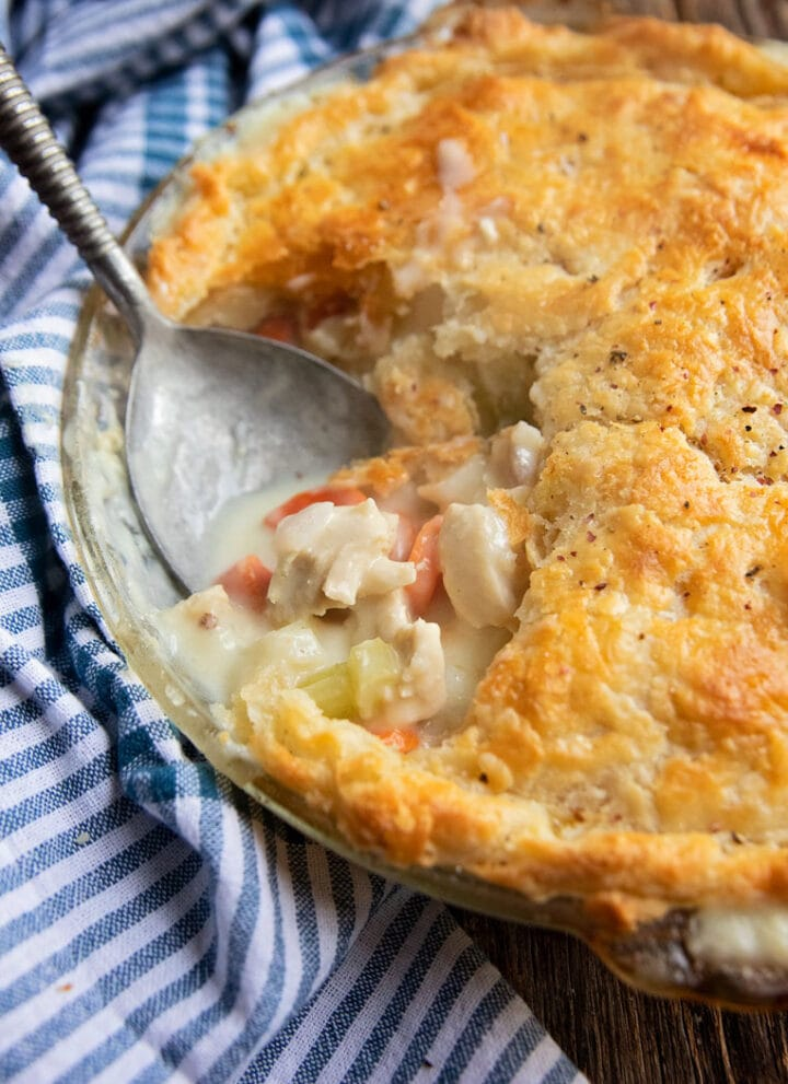 a pie plate of chicken pot pie with a scoop out and a spoon in it