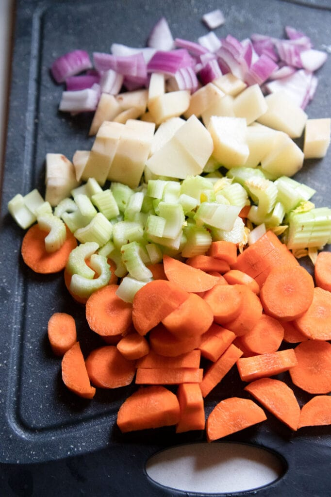 a cutting board of diced vegetables (carrots, celery, onions, and potatoes)