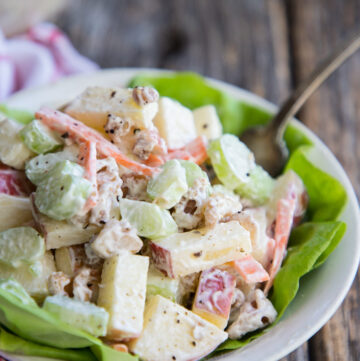 A bowl of Waldorf salad in a bowl with a fork and lettuce