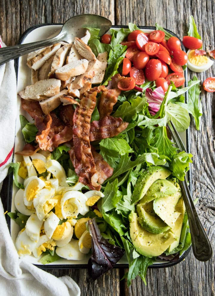 platter cobb salad with avocado, tomatoes, eggs and bacon and grilled chicken