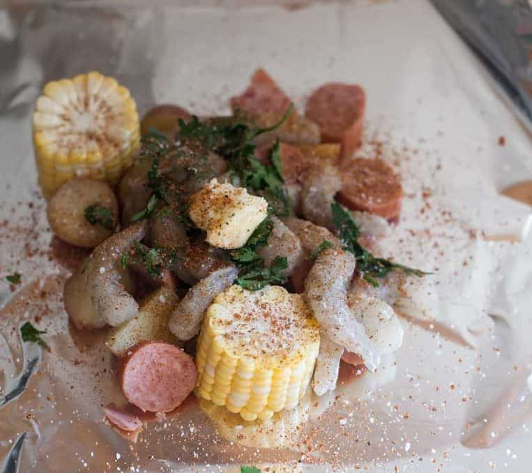 a foil sheet piled with corn, shrimp, sausage, herbs and dotted with butter before baking