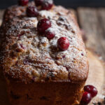 cranberry bread with walnuts and orange on a board