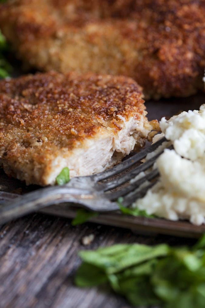 a sliced parmesan turkey cutlet on a plate