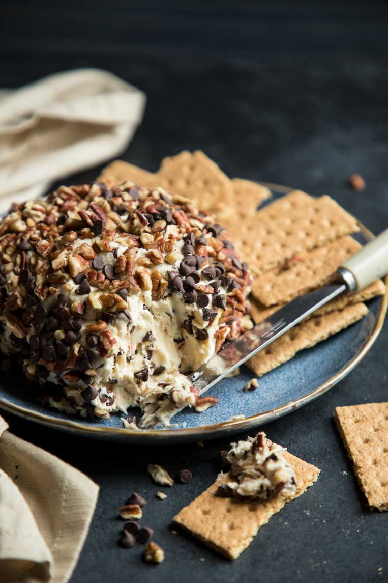 a chocolate chip dessert cheese ball on a plate with a knife and graham crackers