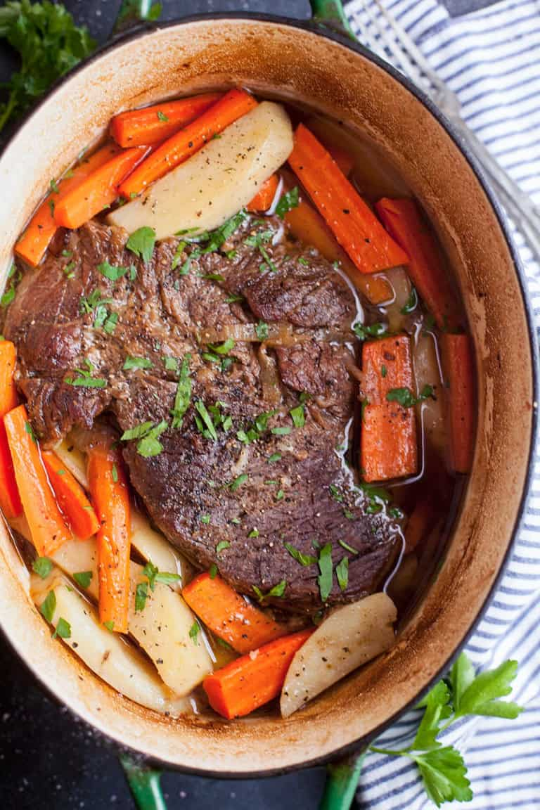 a dutch oven with a cooked pot roast surrounded by potatoes and carrots on a table