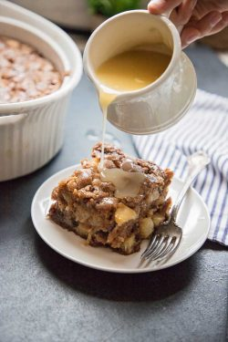 fresh apple cake with vanilla cream sauce being poured over it from a pitcher