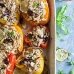 Greek stuffed peppers in a white dish with basil.