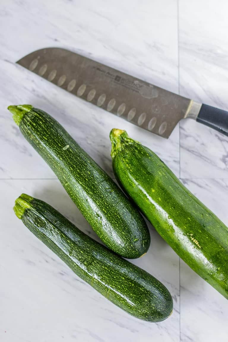 Zucchini on a board next to a knife.