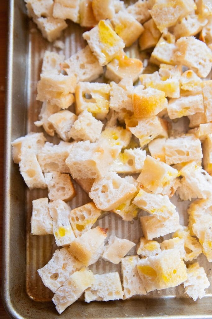 a plate of crouton cubes on a cookie sheet with olive oil drizzled