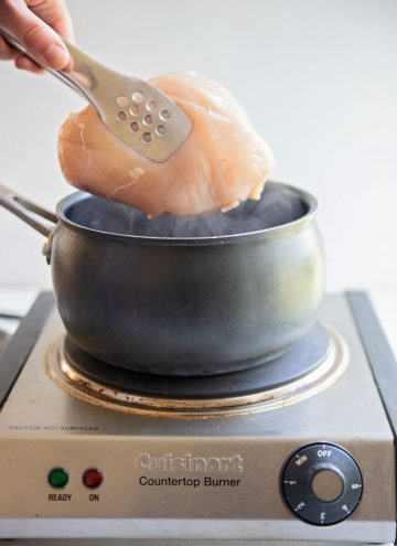 a pot of boiling water with a chicken breast being placed inside