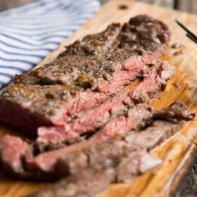 a skirt steak sliced open on a cutting board to show the pink interior
