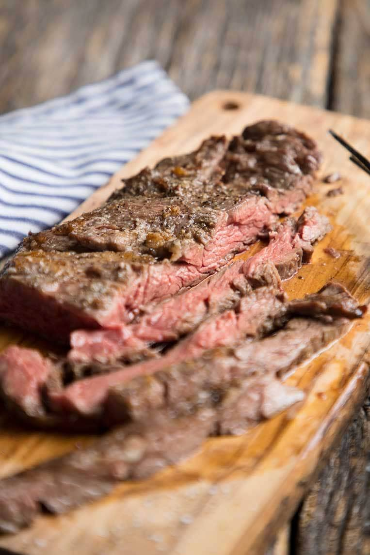 a broiled skirt or flank steak sliced on a wooden cutting board on a blue napkin