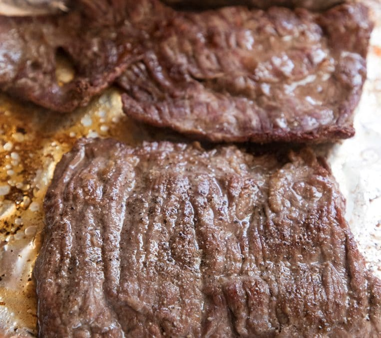 a broiled skirt steak resting on its baking sheet before cutting