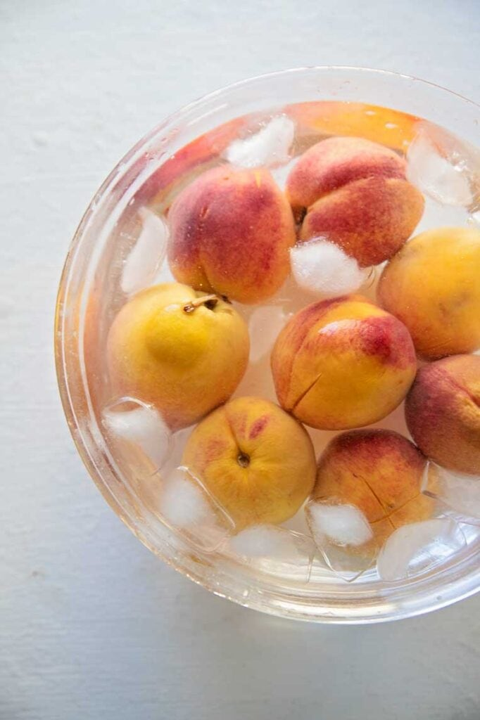 a bowl of ice water with peaches in it