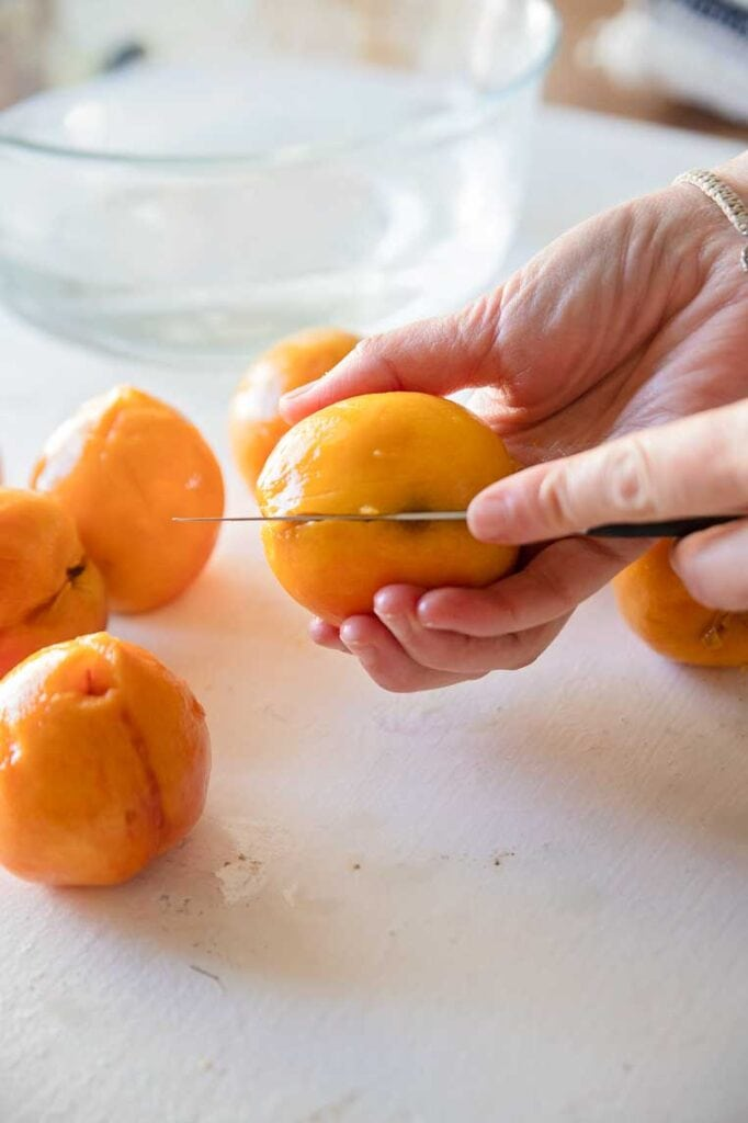 a knife slicing open a peeled peach