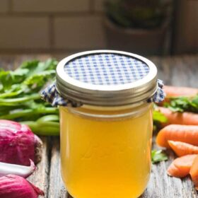 How to make homemade chicken stock. A jar of chicken stock on a table with vegetables.
