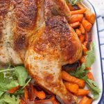 A roast chicken on a tray with carrots