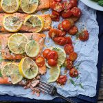 baked salmon filet on a sheet pan with tomatoes and lemons