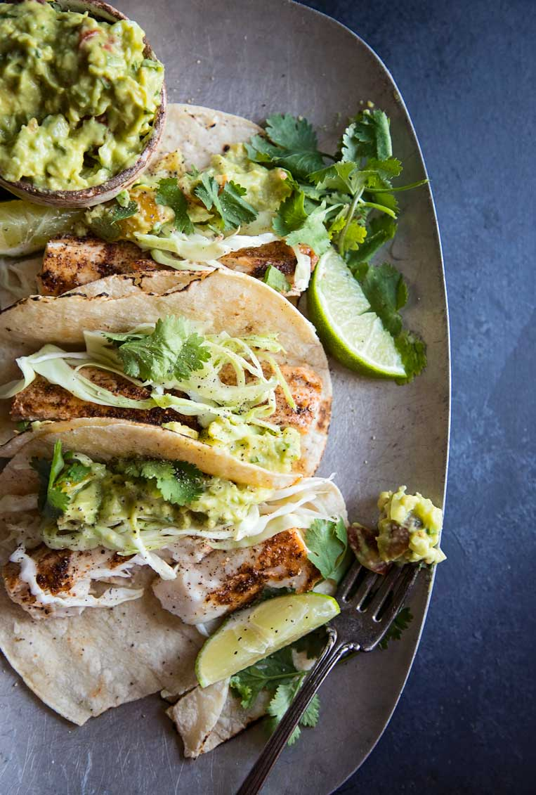 Easy grilled fish tacos piled together on a plate with chunky avocado cream