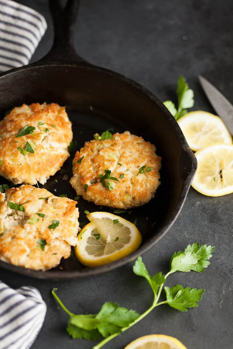crab cakes in a pan with a lemon slice with parsley on the side