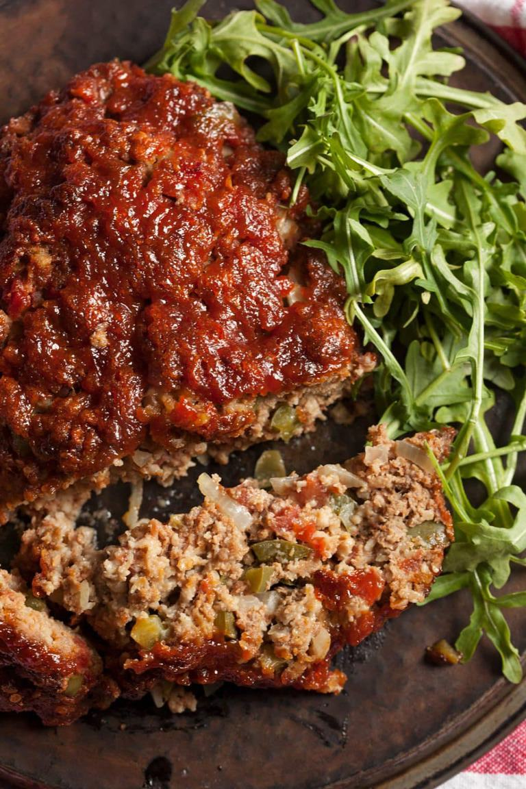 An overhead shot of sliced meatloaf on a platter with green salad