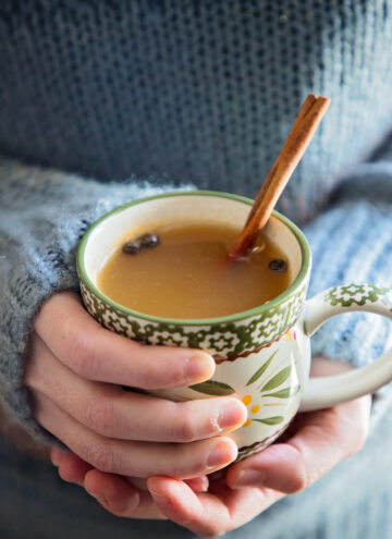 holding a mug of mulled cider with a cinnamon stick.