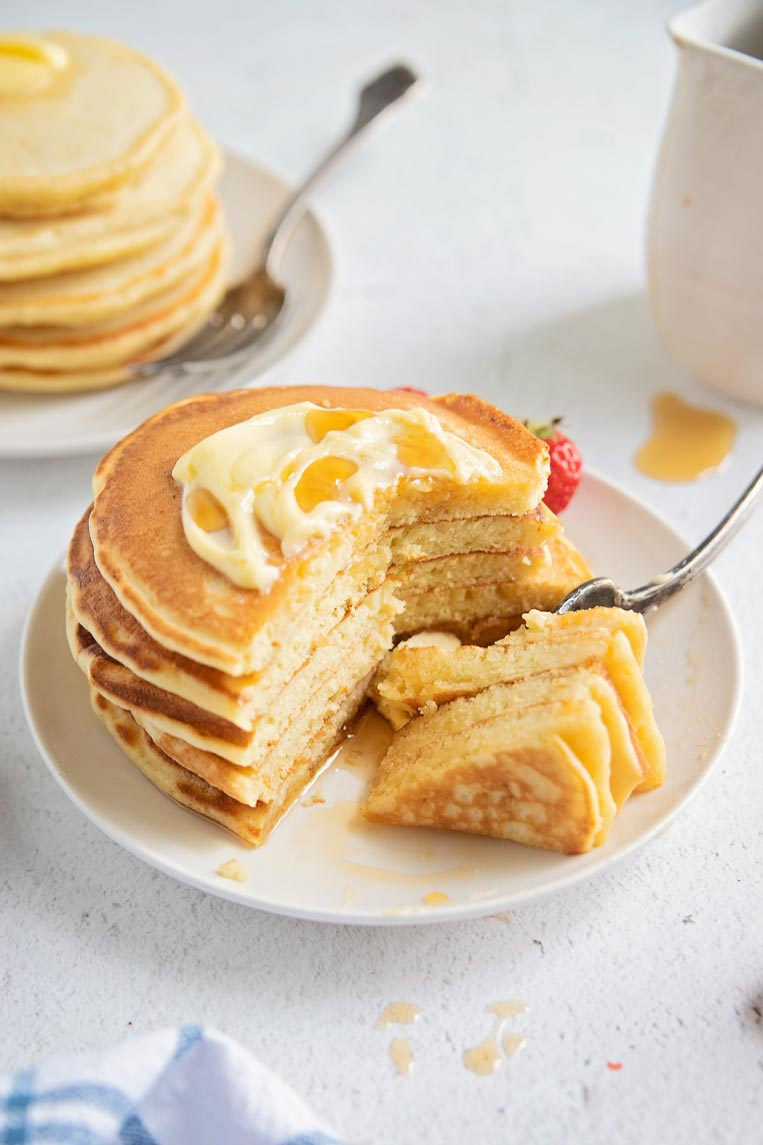 a stack of sliced pancakes on a plate with a  fork