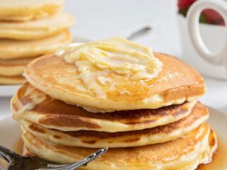 a stack of whole pancakes with syrup and butter on a plate