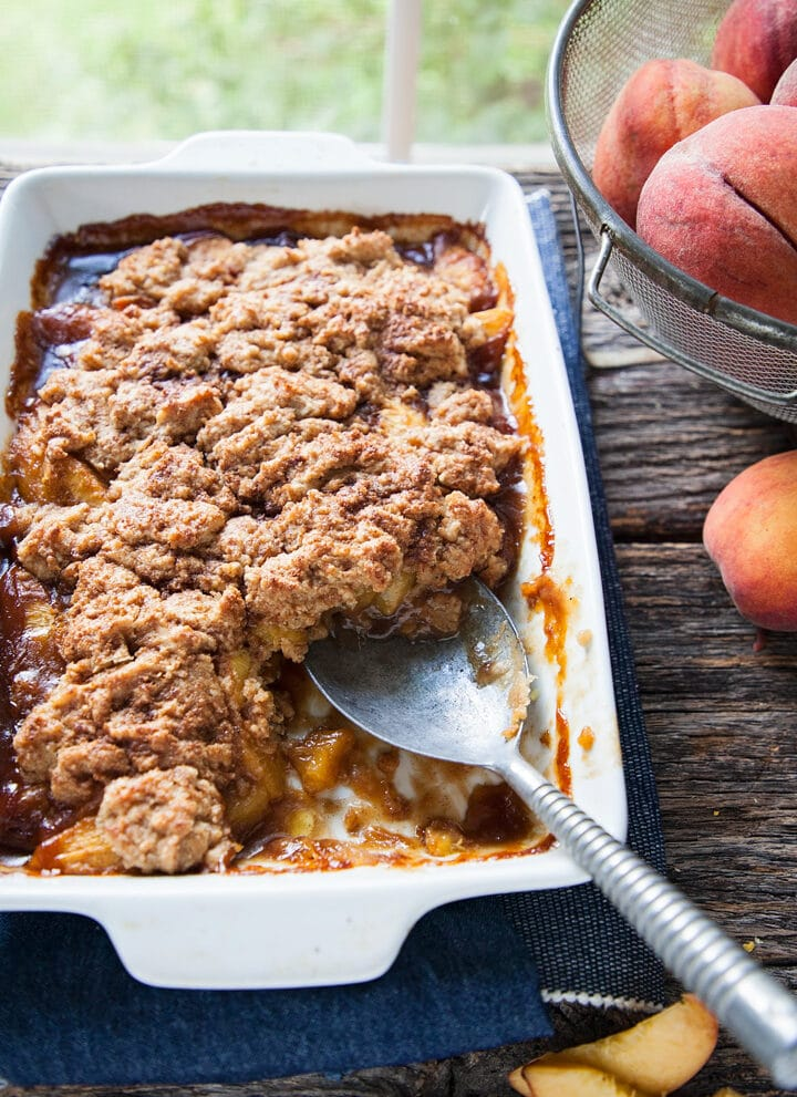 a big pan of fresh peach cobbler with a spoon in it by a window