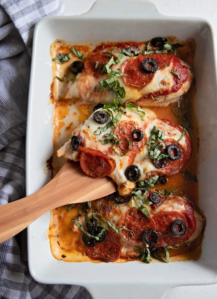 pizza baked chicken breasts in a baking dish with a spatula