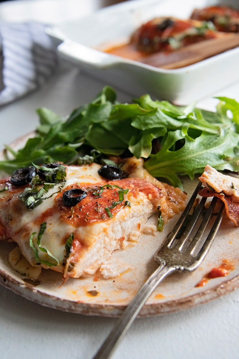 a sliced pizza baked chicken breast on a plate with salad