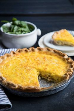 Quiche Lorraine in a pie plate with a slice taken out.