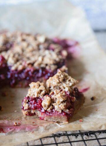a cut healthier raspberry crumble bar on parchment paper